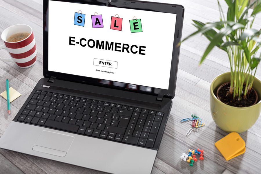 the words Sale and ECommerce on a laptop screen with an enter button. There is a plant on the right side of laptop and a cup of coffee on the left side.