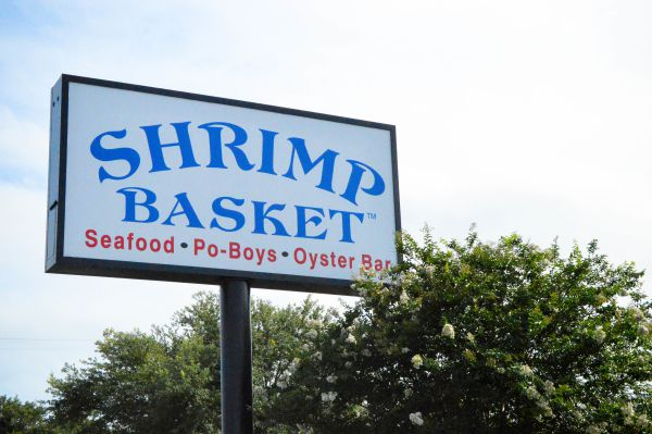 Outdoor location sign featuring blue Shrimp Basket logo