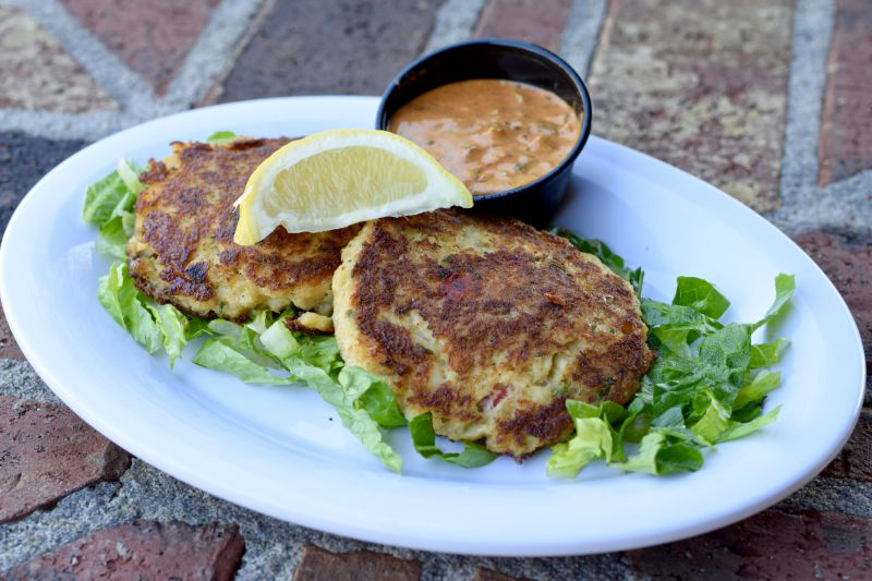 two crab cakes on a bed of greens with a side of remoulade