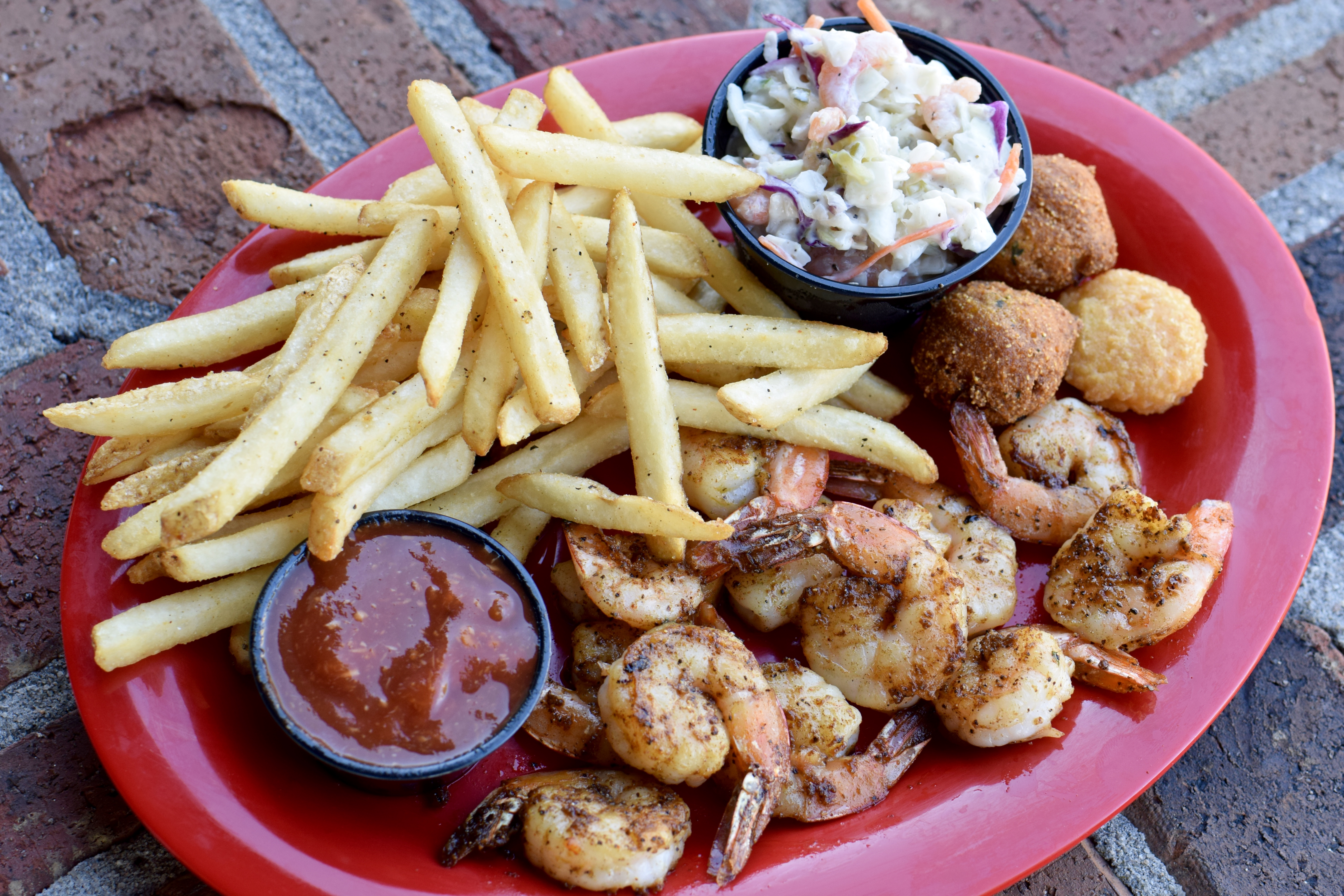 Grilled shrimp platter with cocktail sauce and a side of fries & hush puppies
