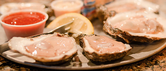 Platter of a dozen fresh, raw oysters on the half shell