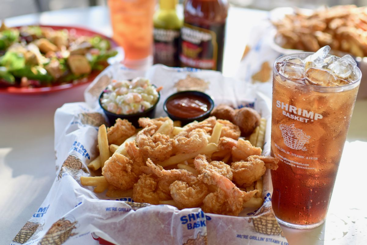 Basket of fried shrimp with fries, cole slaw, cocktail sauce and a glass of tea