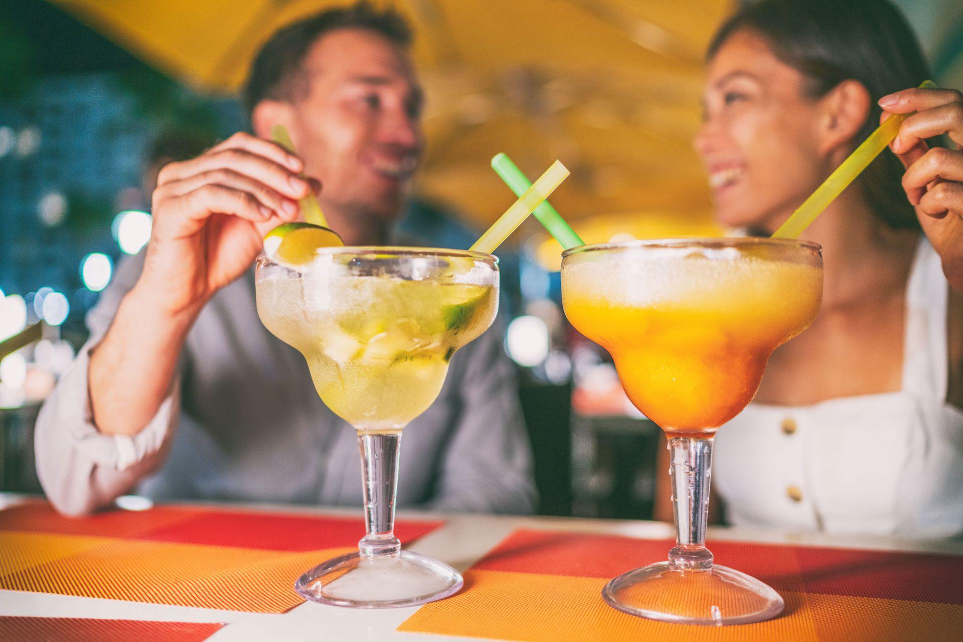 Two people sitting at a bar enjoying a glass of margarita