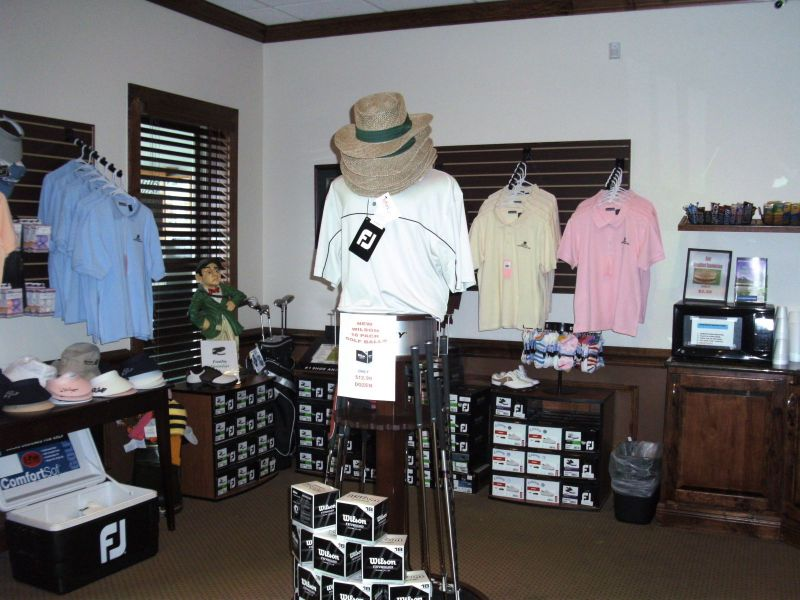 View from inside the Pro Shop showing shirts, shoes, and golf clubs