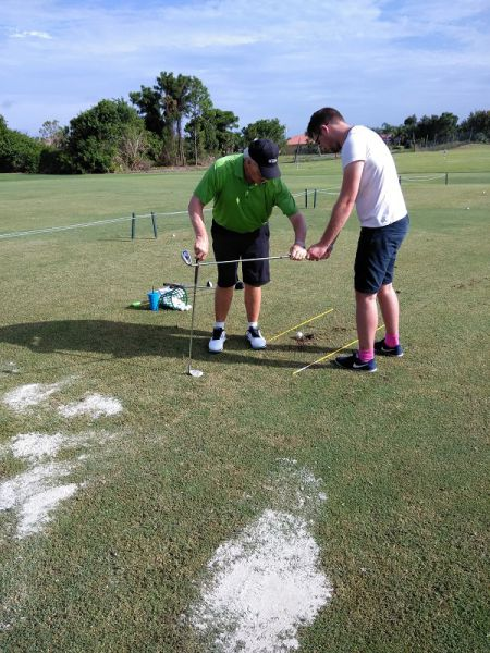 Rick Anderson helping a golf student with his swing