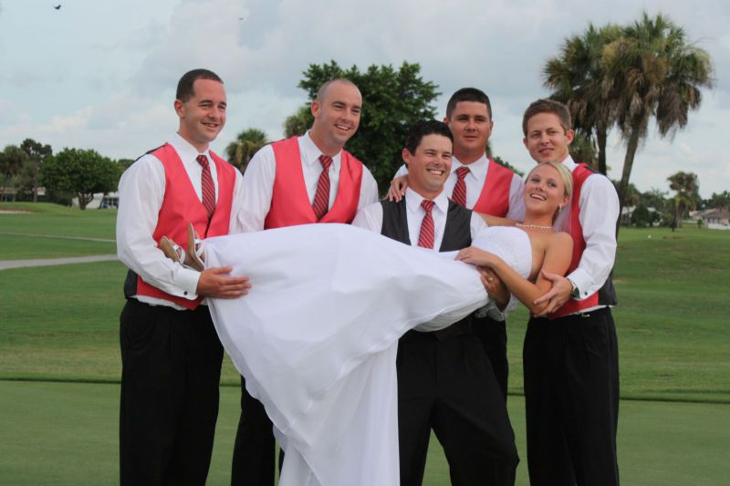 Groom and groomsmen holding the bride