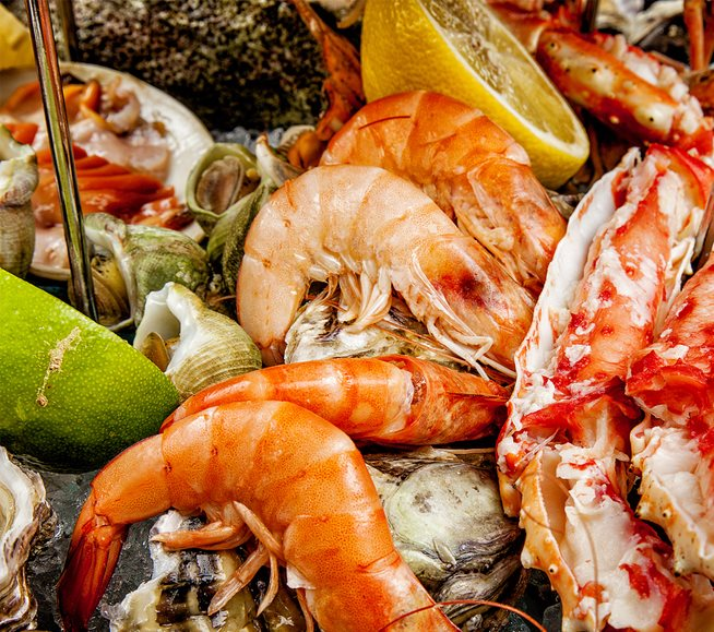colorful pile of cooked seafood, shrimp, citrus and more