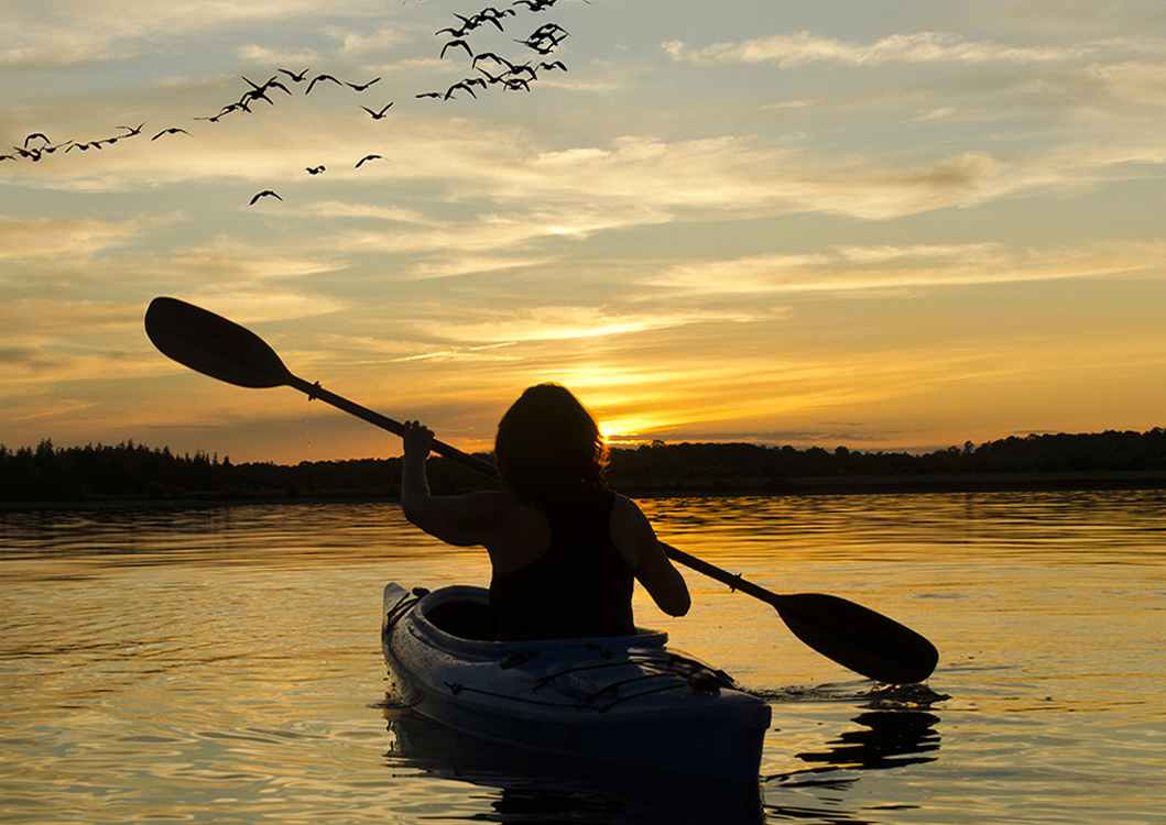 sillouette of woman kayaking into the sunset