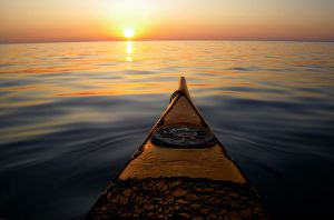 front of kayak in water facing sunset on horizon