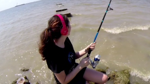 young girl with headphones sits on rock fishing