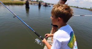 two young boys fishing off a dock