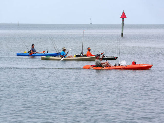 three men spead out on water in kayaks