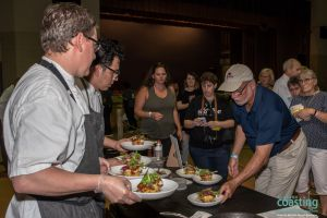 event volunteers carry finished dishes from chef to judging table