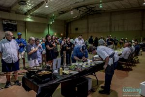 chef plates dishes on table in front of big crowd of attendees