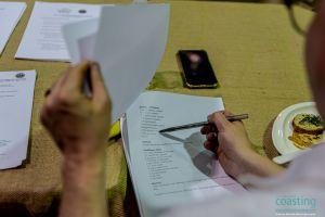close-up of hand writing dish score down on judging sheet