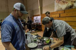event host watches as chef plates the last of his dishes for food competition