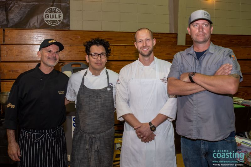 Four male chefs stand in row in front of convention wall