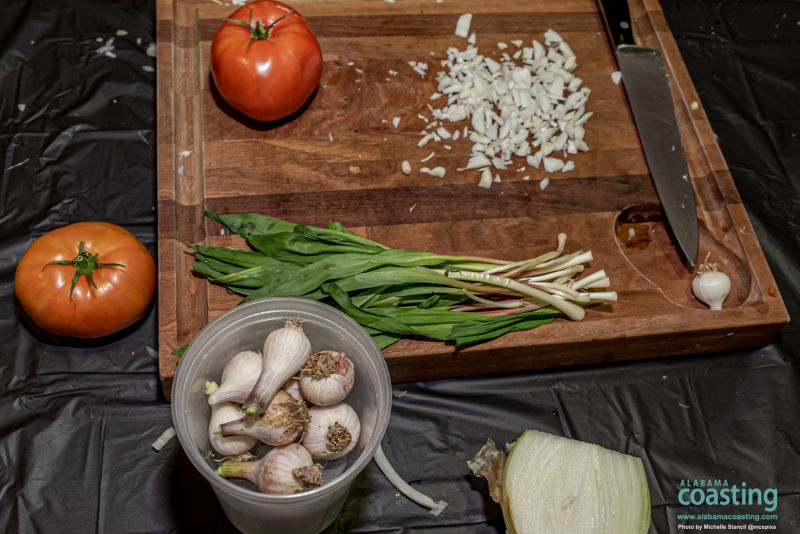 wooden cutting board with onions, tomatoes, garlic and more in process of being chopped