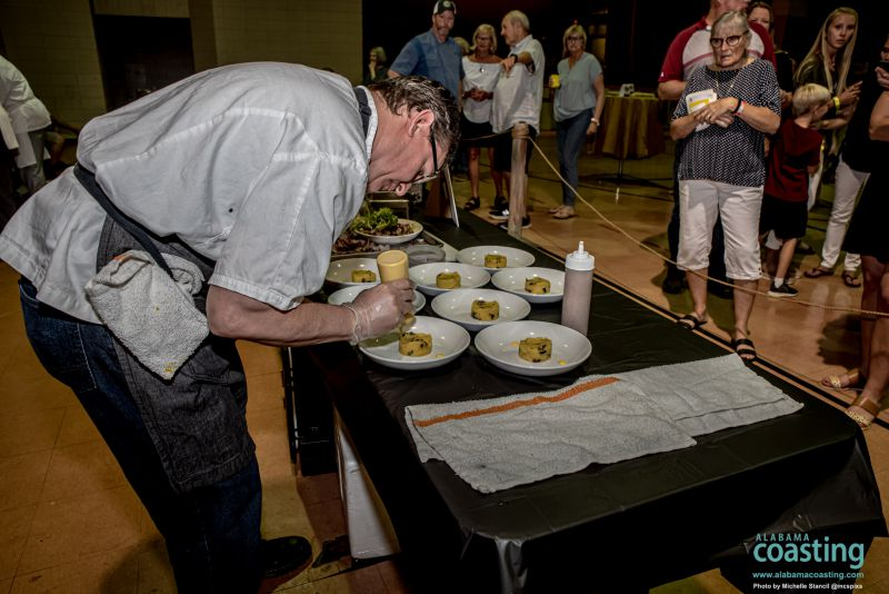 Chef bent over dishes on table in middle of convention hall
