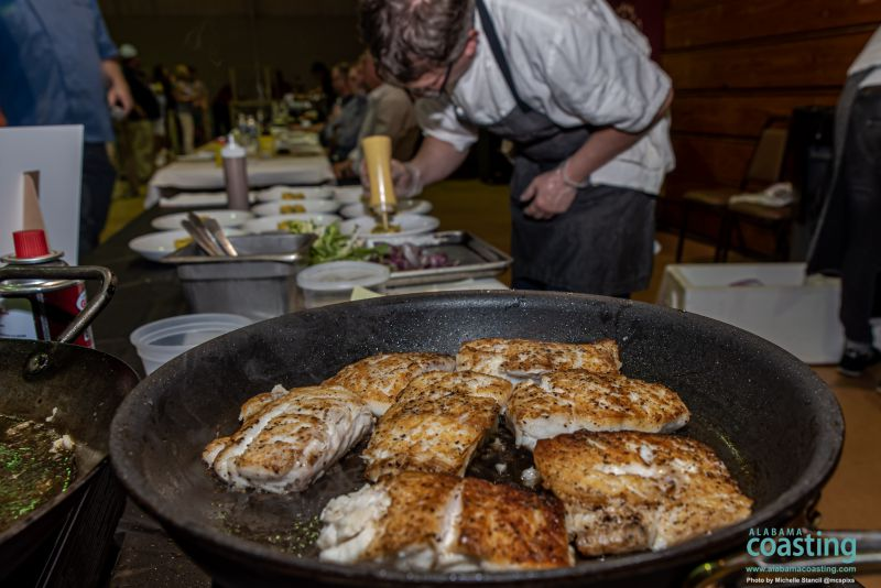 skillet full of crispy fish filets with chef preparing other dishes in background