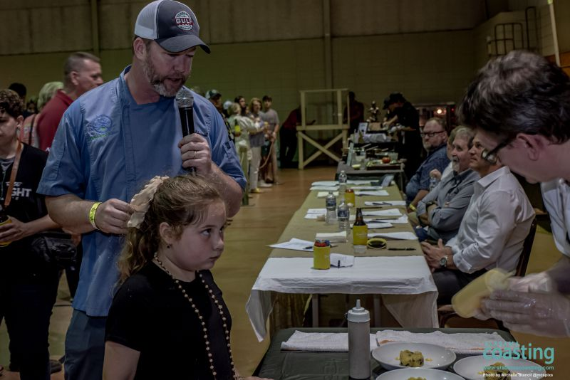 Guy with microphone and little girl looking at food booth in convention hall