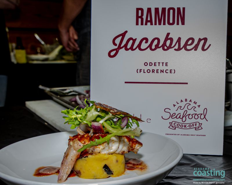 Colorful fish dish sitting in front of sign for chef Ramon Jacobsen