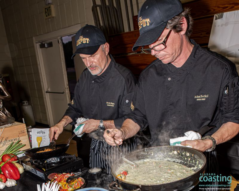 two male chefs in black coats cook over big wok in convention hall