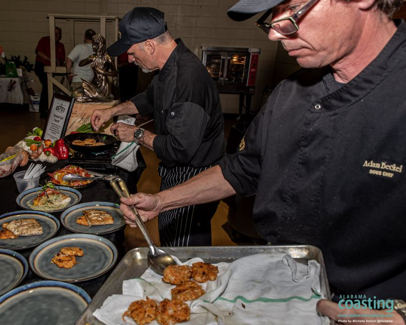 Chefs in black coats plating dishes at food booth