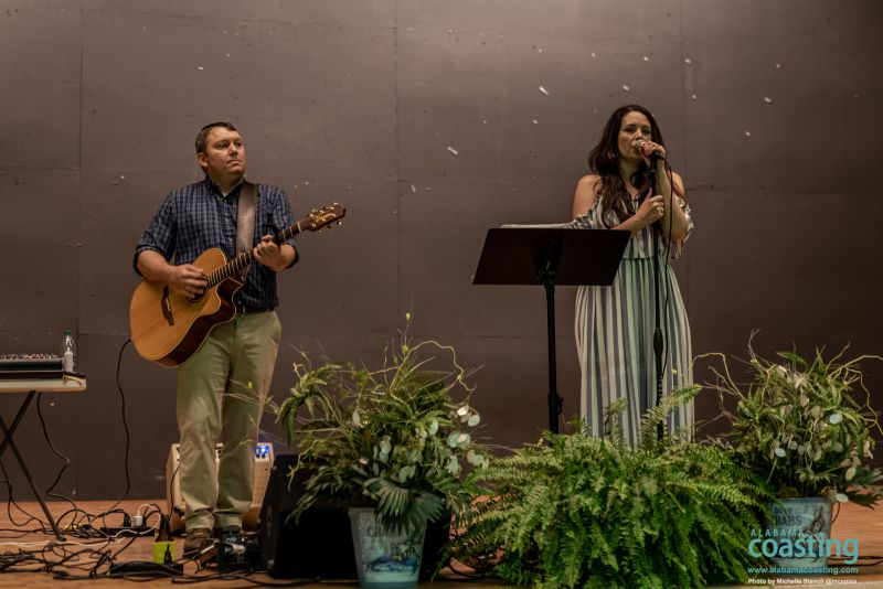 man and woman on stage singing at event