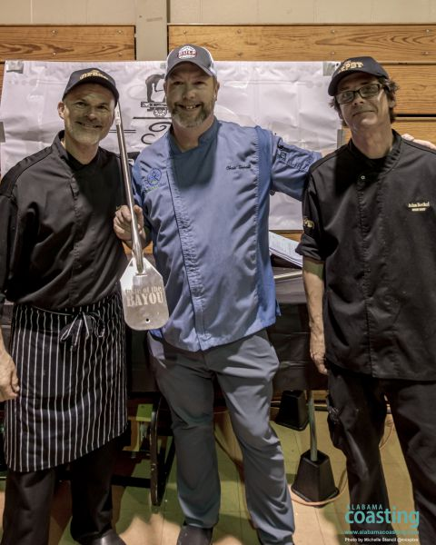 event host poses with two of the event chef winners