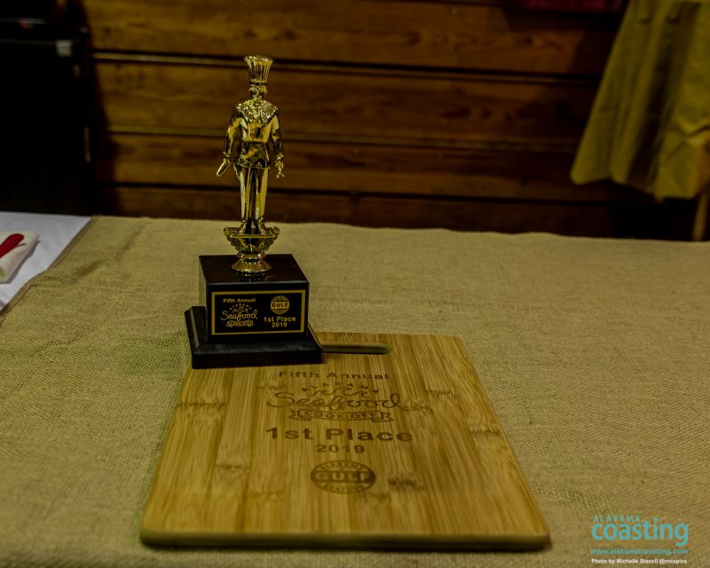 wooden plaque and golden trophy featured on awards table at event