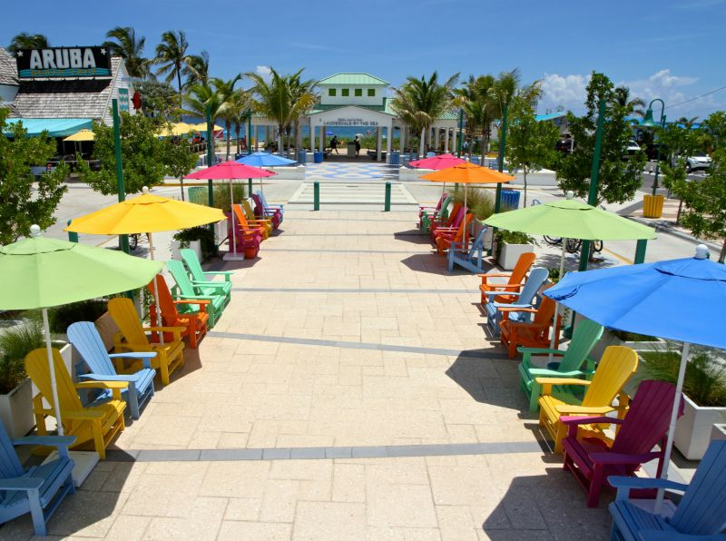 Downtown boardwalk with different brightly colored beach umbrellas and chairs.