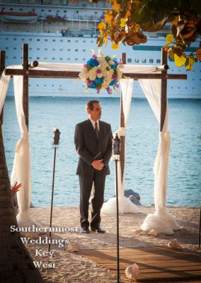Officiant stands under a wedding arch as a cruise ship passes in the background