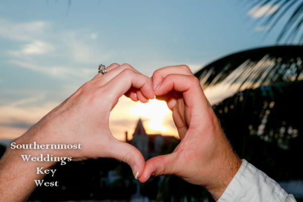 Couple making a heart shape with their hands and the sunset is showing through