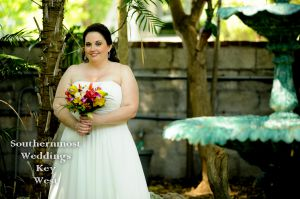 A bride poses for photos before the wedding in a historic Key West Tropical Garden