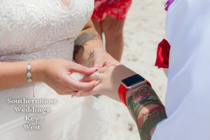 Wedding couple exchanges rings on the beach