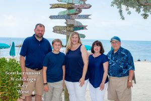 Family poses in front of Mile Marker Sign at Ft. Zachary Taylor
