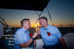 Gay Wedding Couple Toast Champagne on a Private Sailboat by Southernmost Weddings Key West