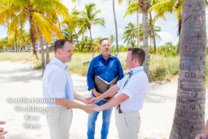 Gay Wedding Couple exchange vows on Smathers Beach by Southernmost Weddings Key West