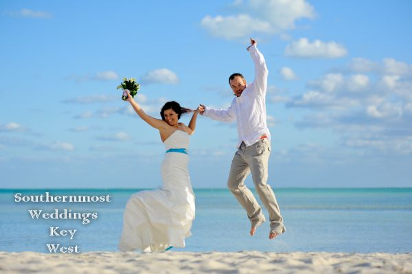 Wedding Couple jumping to celebrate their marriage on Smathers Beach in Key West, Florida