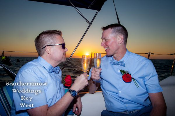 Two Men Toasting Champagne on a Sailboat with the sun setting in the background