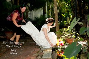 Brides assistant helps with the wedding dress - Image by Southernmost Weddings
