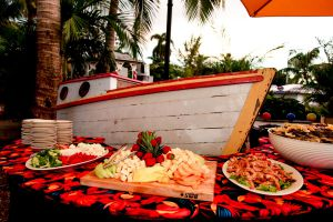 Wedding reception buffet laid out in front of an old time sailing vessel