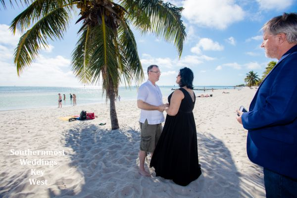 Wedding couple getting married under a palm tree on Smathers Beach in Key West, Florida