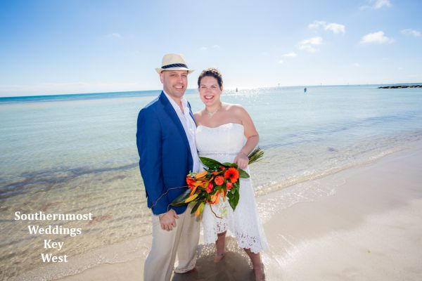 Wedding couple poses next to the ocean on Smathers Beach in Key West, Florida