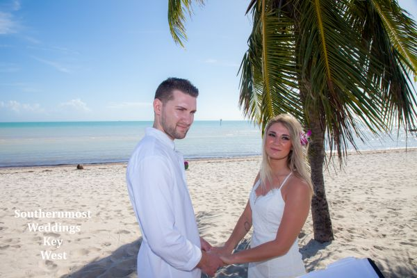 Wedding couple getting married under a palm tree on Smathers Beach