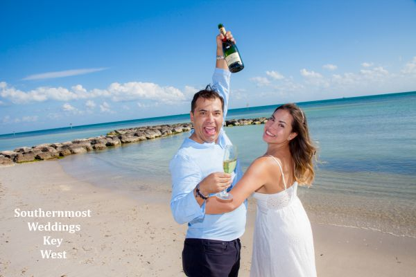 Wedding couple celebrate their wedding with a champagne toast on Smathers Beach