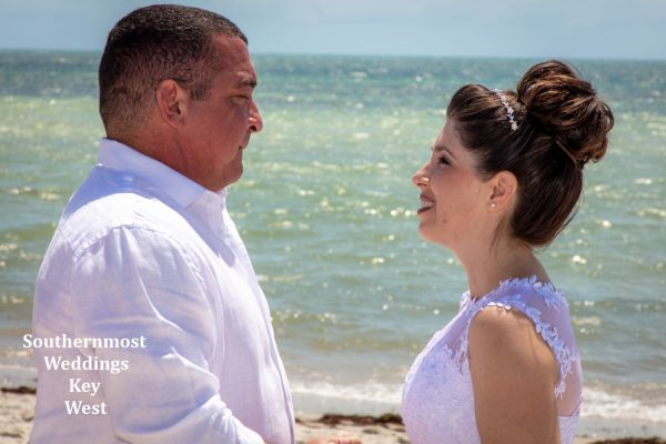 Wedding couple poses for photos on Smathers Beach in Key West, FL.