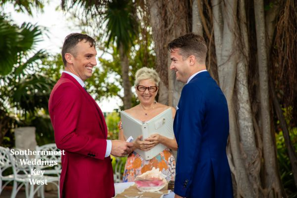 Wedding officiant performs a wedding ceremony under the Banyan Tree in the West Martello Garden