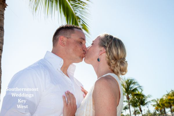Wedding couple kiss under a palm tree after their Romantic Beach Elopement planned by Southernmost Weddings